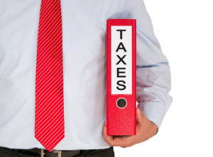 """A picture of a businessman holding a binder labeled """"taxes."""""""