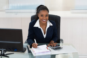 Smiling businesswoman calculating bills at office desk